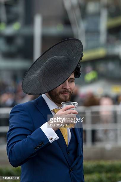 A racegoer wears a female companion's hat as he attends Ladies Day the second day of the Grand National Festival horse race meeting at Aintree...