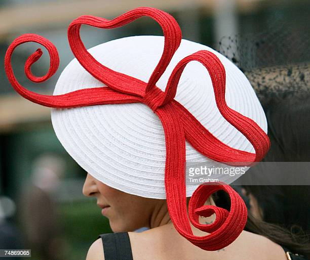 Racegoer wears a traditional Ascot style white hat with red heartshaped bows and a backless dress to show off her star tattoos on the second day of...