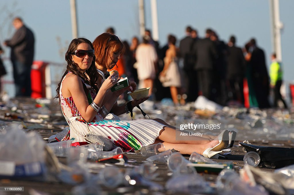 Racegoers are seen as they leave the racecourse after Ladies' Day at Aintree Racecourse on April 8, 2011 in Liverpool, England.