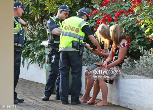 Racegoers are spoken to by police officers as they take a rest as they make their way from the course following 2017 Oaks Day at Flemington...