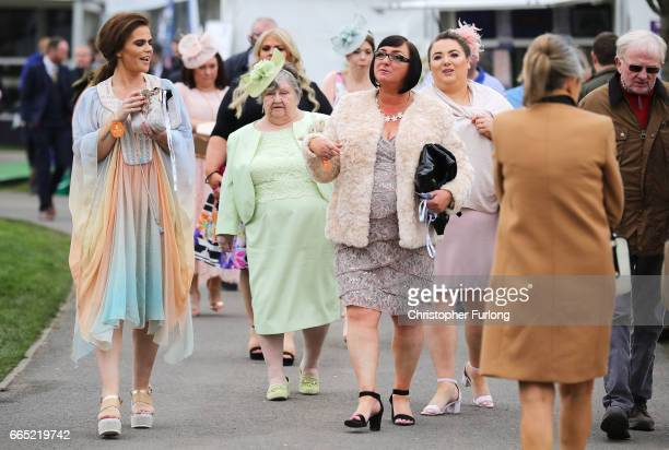 Racegoers arrive for the opening day of the Randox Health Grand National Festival at Aintree Racecourse on April 6 2017 in Liverpool England Today is...