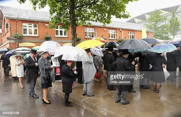 Racegoers arrive in torrential rain at Royal Ascot 2016 at Ascot Racecourse on June 14 2016 in Ascot England