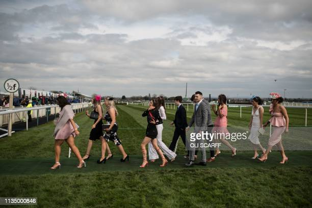 TOPSHOT Racegoers arrive to attend Ladies Day the second day of the Grand National Festival horse race meeting at Aintree Racecourse in Liverpool...