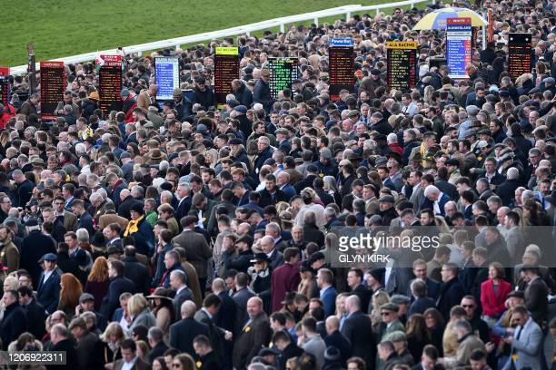 Racegoers attend the final day of the Cheltenham Festival horse racing meeting at Cheltenham Racecourse in Gloucestershire, south-west England, on...