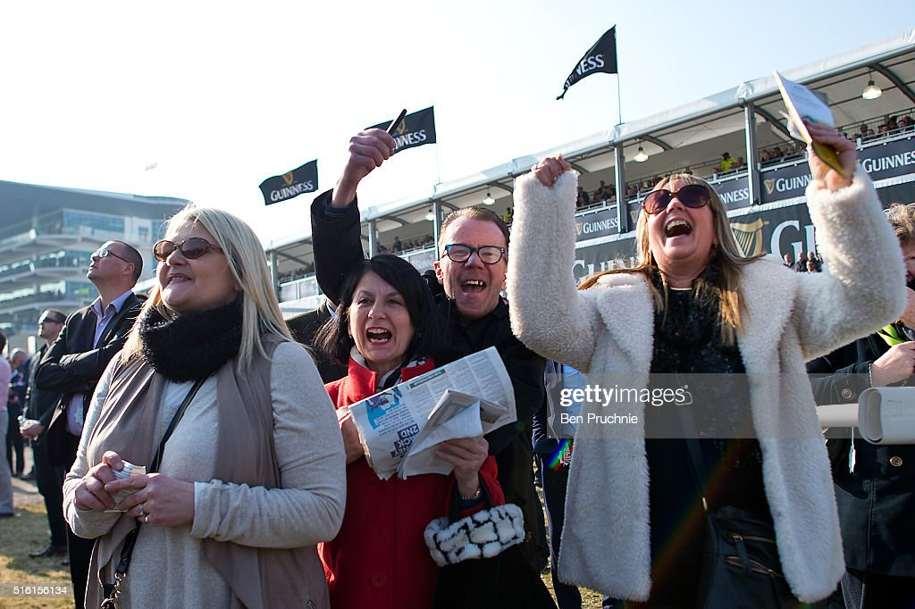Racegoers celebrate after watching the Ryanair steeple chase during St Patrick's Day at the Cheltenham Festival at Cheltenham Racecourse on March 17, 2016 in Cheltenham, England. The four day annual jump racing event sees jockeys compete for a piece of the 4.1 million GBP of the prize money.