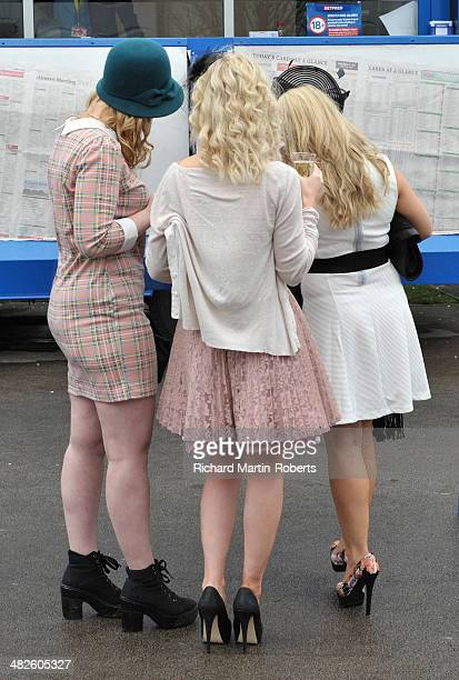 Racegoers check the form on Day 2 Ladies Day of the Aintree races at Aintree Racecourse on April 4 2014 in Liverpool England