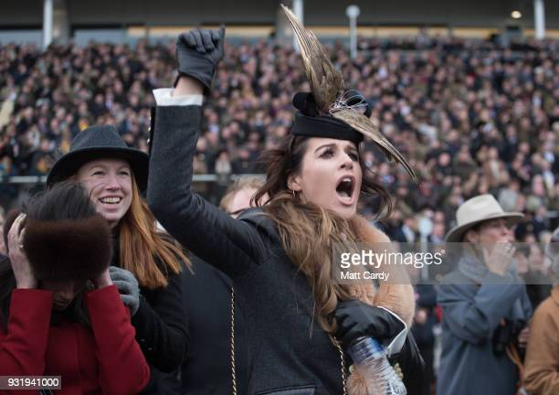 Racegoers cheer and react as they watch the Queen Mother Champion Steeple Chase on Ladies Day at the Cheltenham Racecourse on March 14 2018 in...