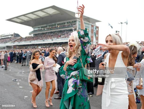 Racegoers cheer as they watch the racing on day two 'Ladies Day' of The Randox Health Grand National Festival at Aintree Racecourse on April 13 2018...