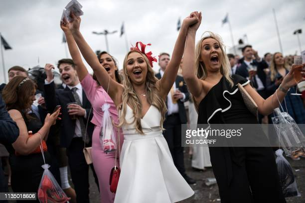 Racegoers cheer as they watch the racing on Ladies Day, the second day of the Grand National Festival horse race meeting at Aintree Racecourse in...