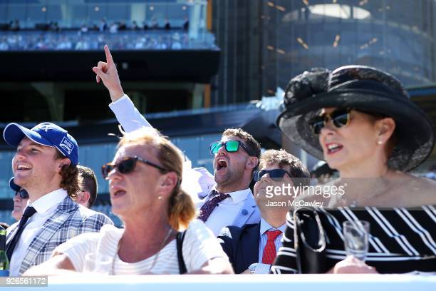 Racegoers cheer as Winx riden by Hugh Bowman races in The TAB Chipping Norton Stakes during Sydney Racing at Royal Randwick Racecourse on March 3...