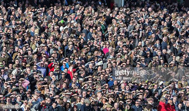 Racegoers cheer during the Arkle Challenge Trophy at Cheltenham Racecourse on the first day of the Cheltenham Festival on March 10 2015 in Cheltenham...