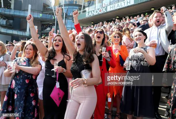 Racegoers cheer during the final day of the Grand National Festival horse race meeting at Aintree Racecourse in Liverpool northern England on April...