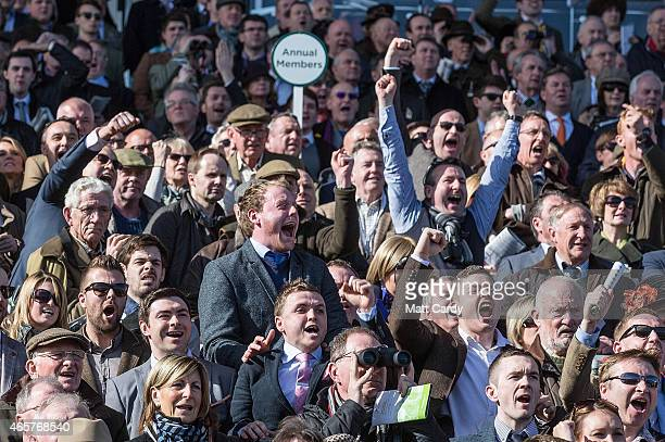 Racegoers cheer during the first race at Cheltenham Racecourse on the first day of the Cheltenham Festival on March 10, 2015 in Cheltenham, England....