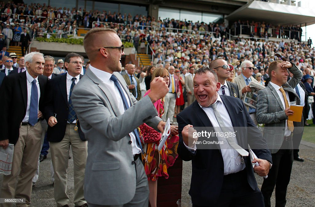 Racegoers cheer home a winner at Goodwood on July 26, 2016 in Chichester, England.