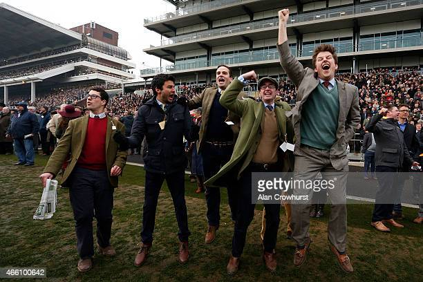 Racegoers cheer home a winner during Gold Cup day at the Cheltenham Festival at Cheltenham racecourse on March 13 2015 in Cheltenham England