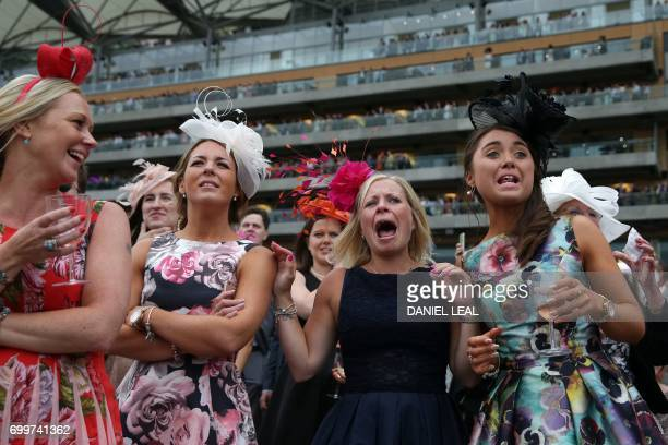 TOPSHOT Racegoers cheer on their horse on Ladies Day at the Royal Ascot horse racing meet in Ascot west of London on June 22 2017 The fiveday meeting...