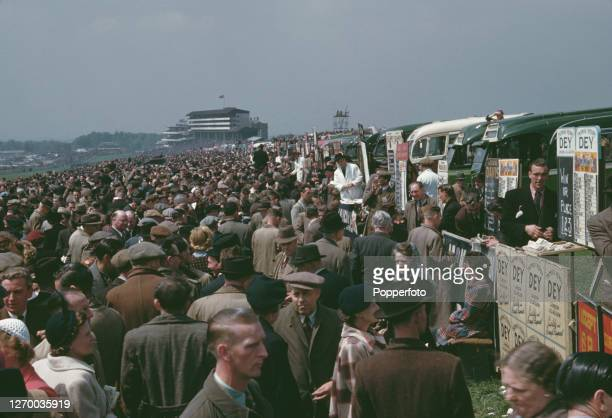 Racegoers crowd around on-course bookmakers stands to place their bets with bookies during the Epsom Derby race meeting at Epsom Downs racecourse in...