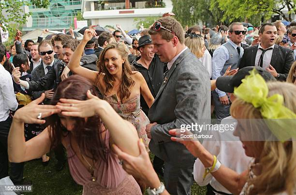 Racegoers dance as a band plays music after the Melbourne Cup at Flemington Racecourse on November 6 2012 in Melbourne Australia