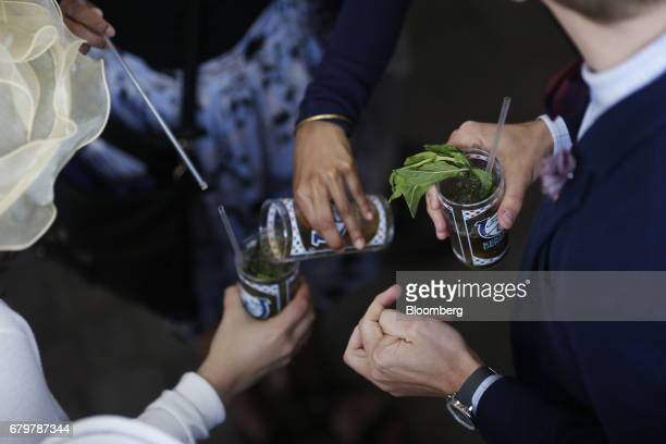 Racegoers drink mint julep cocktails before the 143rd running of the Kentucky Derby at Churchill Downs in Louisville Kentucky US on Saturday May 6...