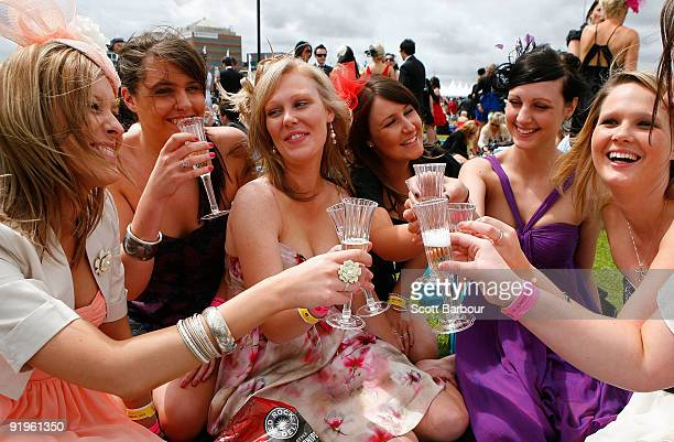 Racegoers enjoy a drink of champagne during the Caulfield Cup Day meeting at Caulfield Racecourse on October 17 2009 in Melbourne Australia