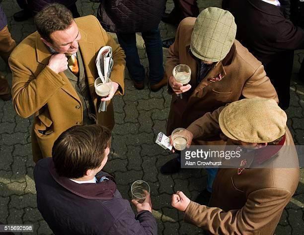 Racegoers enjoy a Guinness before racing at Cheltenham racecourse on March 15 2016 in Cheltenham England