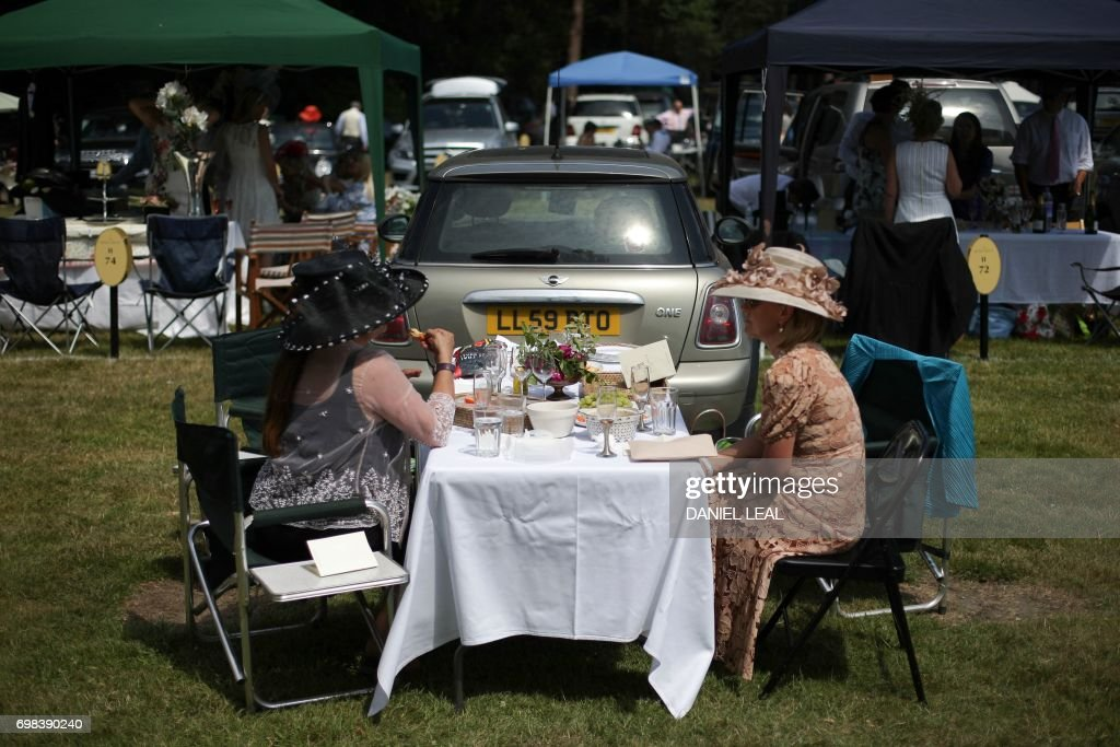 Racegoers enjoy lunch in the car park ahead of the horse racing on day one of the Royal Ascot horse racing meet, in Ascot, west of London, on June 20, 2017. The five-day meeting is one of the highlights of the horse racing calendar. Horse racing has been held at the famous Berkshire course since 1711 and tradition is a hallmark of the meeting. Top hats and tails remain compulsory in parts of the course while a daily procession of horse-drawn carriages brings the Queen to the course. / AFP PHOTO / Daniel Leal-Olivas