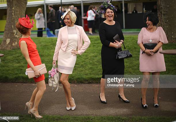 Racegoers enjoy the atmosphere of Ladies Day and dress to impress at the Aintree Grand National Festival meeting on April 4 2014 in Aintree England...
