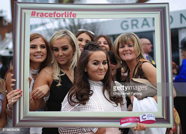 Racegoers enjoy the atmosphere of Ladies Day the second day of the Aintree Grand National Festival meeting on April 8 2016 in Aintree England Today...