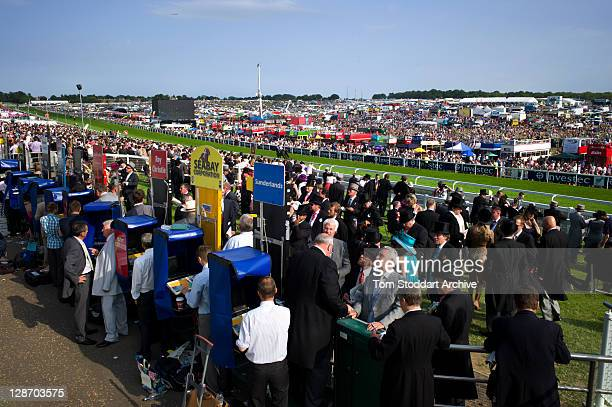 Racegoers enjoy the betting and the atmosphere at the Investec Derby Day held at Epsom Downs Racecourse, Surrey, southern England. The Queen's horse...