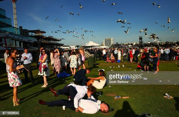 Racegoers fall to the ground as they make their way from the course following 2017 Oaks Day at Flemington Racecourse on November 9 2017 in Melbourne...