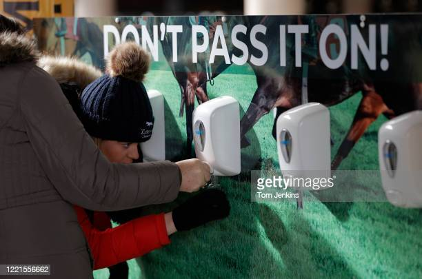 Racegoers filling up their own hand sanitizer bottles from one of the stations placed around the course during day four of the Cheltenham National...