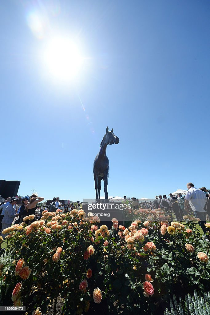 Racegoers gather round the bronze statue of the famous race horse Phar Lap on Melbourne Cup Day at Flemington Racecourse in Melbourne, Australia, on Tuesday, Nov. 5, 2013. The Melbourne Cup, marketed as the race that stops the nation, is Australias premier thoroughbred horse racing event. Photographer: Carla Gottgens/Bloomberg via Getty Images