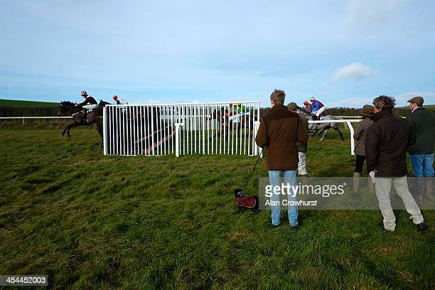 Racegoers get close to a fence to watch the action during the point to point meeting at Barbury Castle racecourse on December 08 2013 in Swindon...