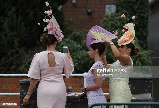 Racegoers help each other with their hats as they arrive on day one of the Royal Ascot horse racing meet in Ascot west of London on June 19 2018 The...