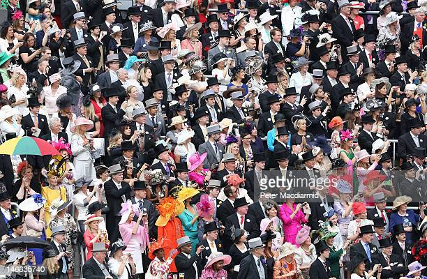 Racegoers in the Royal Enclosure watch the arrival of Queen Elizabeth II in the Parade Ring at Royal Ascot on Ladies Day on June 21 2012 in Ascot...