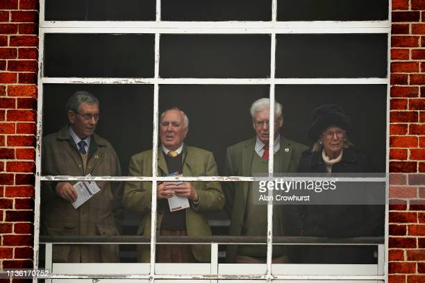 Racegoers keep an eye on the parade ring from the warmth of the grandstand at Kempton Park on March 16 2019 in Sunbury England