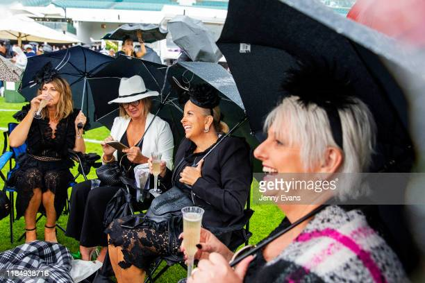 Racegoers laugh as they take refuge under umbrellas as rain falls during 2019 Derby Day at Flemington Racecourse on November 2 2019 in Melbourne...
