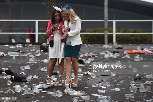 Racegoers leave at the end of Ladies Day of the Grand National Festival horse race meeting at Aintree Racecourse in Liverpool northern England on...