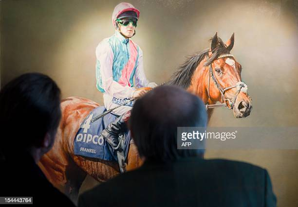Racegoers look at a painting of racehorse Frankel ahead of the Champion Stakes British Champions Middle Distance race at Ascot England on October 20...