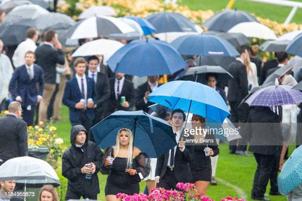 Racegoers make their way through the crowds as rain falls during 2019 Derby Day at Flemington Racecourse on November 2 2019 in Melbourne Australia