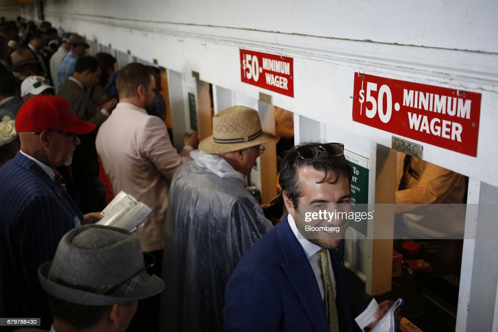 Racegoers place wagers at betting windows before the 143rd running of the Kentucky Derby at Churchill Downs in Louisville, Kentucky, U.S., on Saturday, May 6, 2017. The 143rd running of the Kentucky Derby will feature a field of twenty horses with the winner receiving a gold trophy plus an estimated $1.24 million payday. Photographer: Luke Sharrett/Bloomberg via Getty Images
