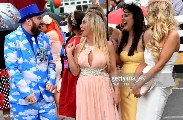 Racegoers pose during Ladies Day of the Grand National Festival horse race meeting at Aintree Racecourse in Liverpool northern England on April 13...