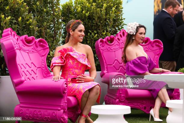 Racegoers pose for a photo taken by a friend during Stakes Day at Flemington Racecourse on November 09 2019 in Melbourne Australia