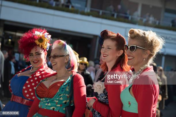 Racegoers pose for a photograph as they arrive at the Cheltenham Racecourse on Ladies Day the second day of the Cheltenham Festival on March 15 2017...