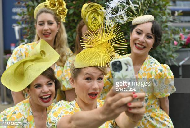 Racegoers pose for a photograph as they attend the fifth day of the Royal Ascot horse racing meet, in Ascot, west of London on June 19, 2021. - Royal...