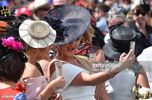 Racegoers pose for a selfie as the horses prepare to take to the track for the 156th running of the Melbourne Cup at Flemington Racecourse in...