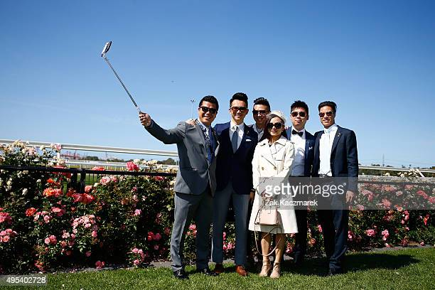 Racegoers pose for a selfie on Melbourne Cup Day at Flemington Racecourse on November 3 2015 in Melbourne Australia