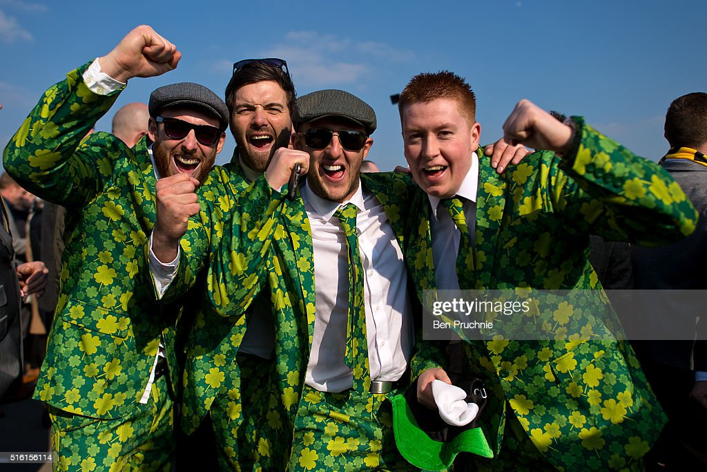 Racegoers pose for photographs wearing shamrock covered suits during St Patrick's Day at the Cheltenham Festival at Cheltenham Racecourse on March 17, 2016 in Cheltenham, England. The four day annual jump racing event sees jockeys compete for a piece of the 4.1 million GBP of the prize money.