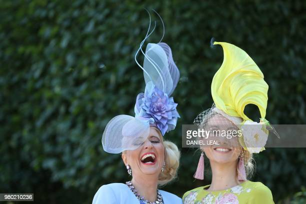 Racegoers pose on Ladies Day at the Royal Ascot horse racing meet, in Ascot, west of London, on June 21, 2018. - The five-day meeting is one of the...