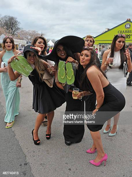 Racegoers pose with flipflops to substitute for their highheels during Day 2 Ladies Day of the Aintree races at Aintree Racecourse on April 4 2014 in...